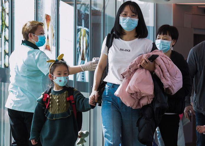 Passagiers uit China worden gescand op het Changi International Airport in Singapore