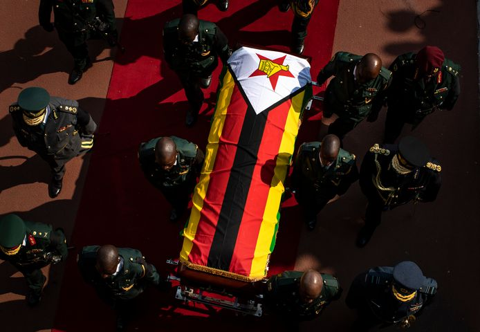 De kist van Mugabe wordt gedragen door enkele militairen.