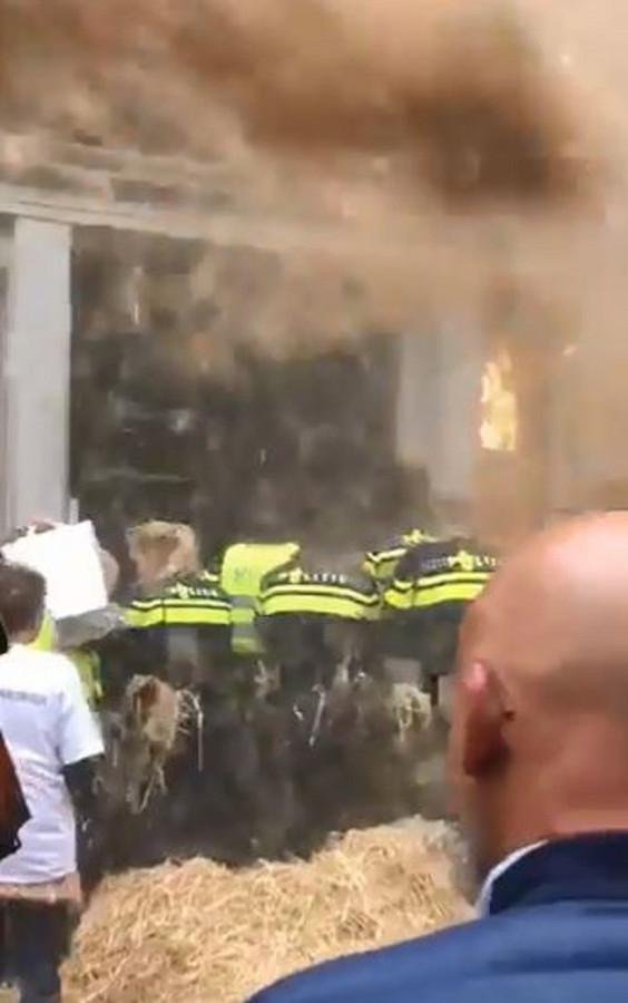 Boze boeren in Groningen geven de politie bij het provinciehuis een strodouche.