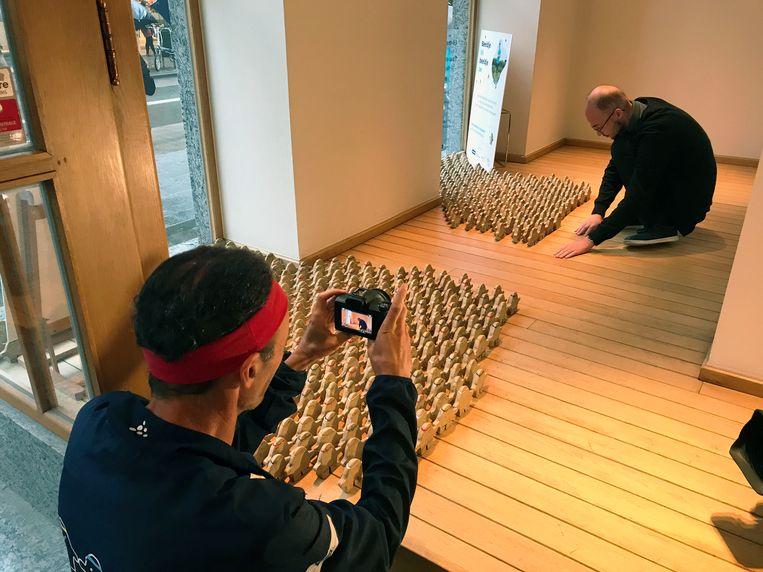 Zoon Pieter zet de beeldjes in de etalage. Vader Johan Swinnen begon met zijn looptochten nadat Pieter genas van een hersentumor.
