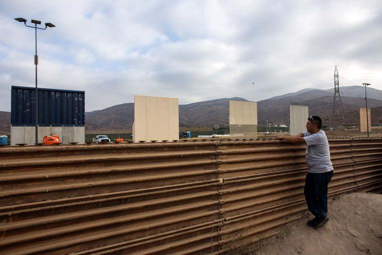 Een man kijkt naar prototypes van de muur van Trump bij de Mexicaanse grens. Beeld afp