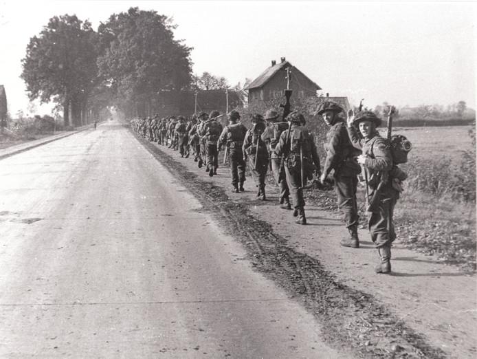 Britse soldaten lopen langs de Rijksweg vanaf de Papendijk in Geffen richting Den Bosch.