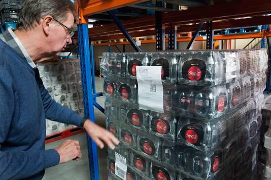 Rob Boswinkel in het distributiecentrum, bij een voorraad Coca-Cola