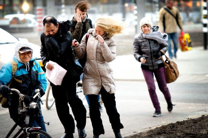 Voetgangers tijdens een voorjaarsstorm. De meeste lezers nemen de waarschuwingen van het KNMI serieus, maar lang niet iedereen blijft thuis bij code geel, oranje of rood.