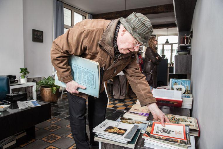 Bezoekers snuisteren tussen de boeken die uitgestald staan in de woonkamer.