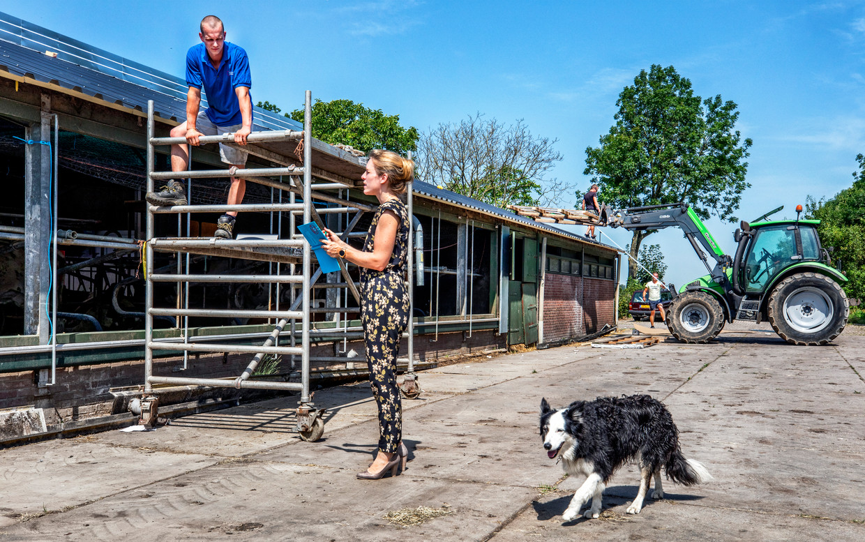 Boer Sander Heikoop (links) in gesprek met Ingeborg Brouwer van Essent. Op de achtergrond wordt de laatste hand gelegd aan het dak.  Beeld Raymond Rutting