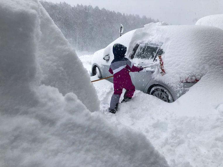 Een jongen maakt een auto schoon in het Oostenrijkse Salzburg. Beeld AFP