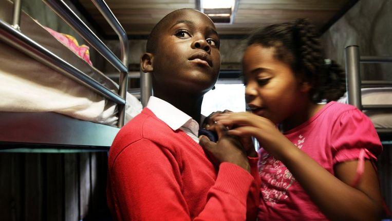 Een leerling krijgt hulp bij het om doen van zijn stropdas bij het nieuwe schooluniform. De particuliere basisschool Bizzie Kids Basic in Almere gaat uniformen verplichten. Beeld anp