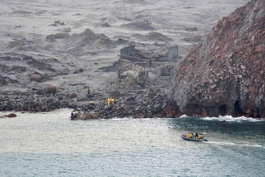 Reddingswerkers op White Island. Het kleine eiland lijkt wel een spookeiland, onder as en lava, helemaal grijs-zwart.