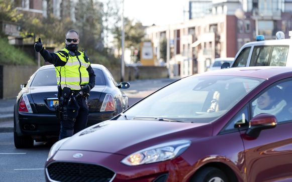 Een Nederlandse agent houdt mensen tegen op toegangswegen naar het strand van Noordwijk. Door het zonnige weer trekken veel mensen erop uit ondanks de coronacrisis. Ter illustratie.