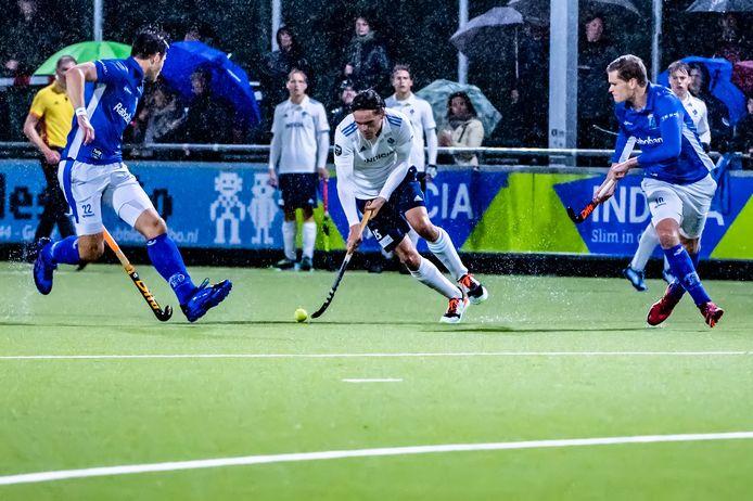 Max Kreft van HC Tiburg (midden) slalomt tussen twee spelers van Kampong door.