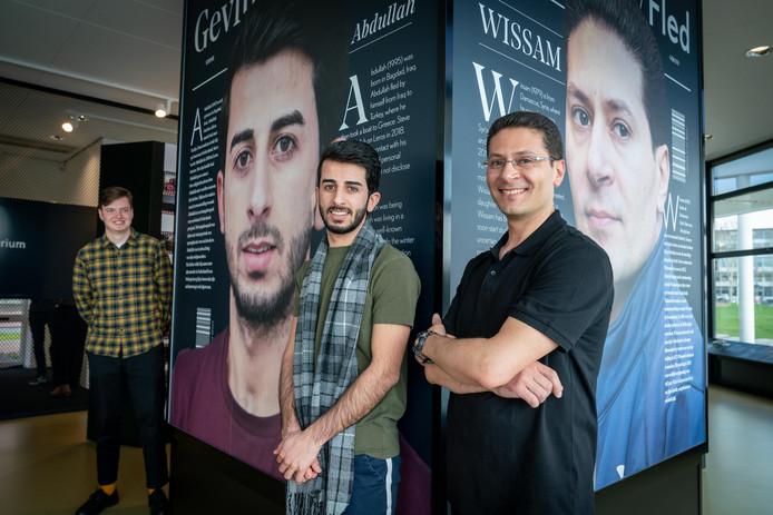 Vluchtelingen Abdullah en Wissam bij hun foto's op de expositie. Links staat fotograaf en filmmaker Steve Gijrath.