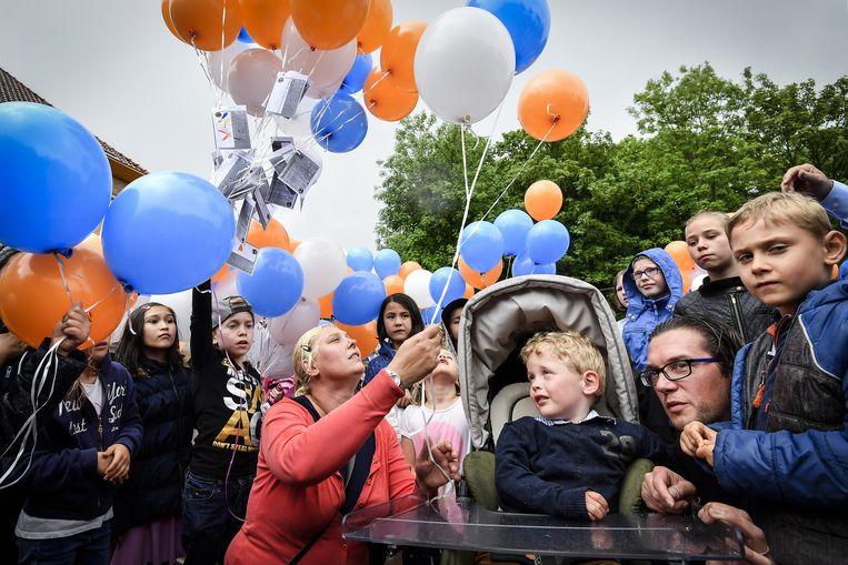 De vierjarige Thor wordt geflankeerd door zijn mama Nancy (links) en papa David (rechts) en omringd door medeleerlingen van zijn broer en zus.