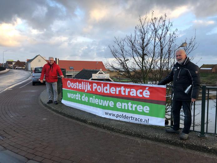Wim Cornelisse en Thijs Mol van de dorpsraad hangen in Yerseke een spandoek op.