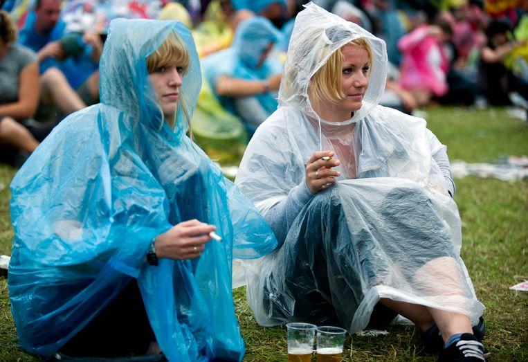 Bezoekers van Lowlands 2010 roken een sigaretje op het gras Beeld ANP