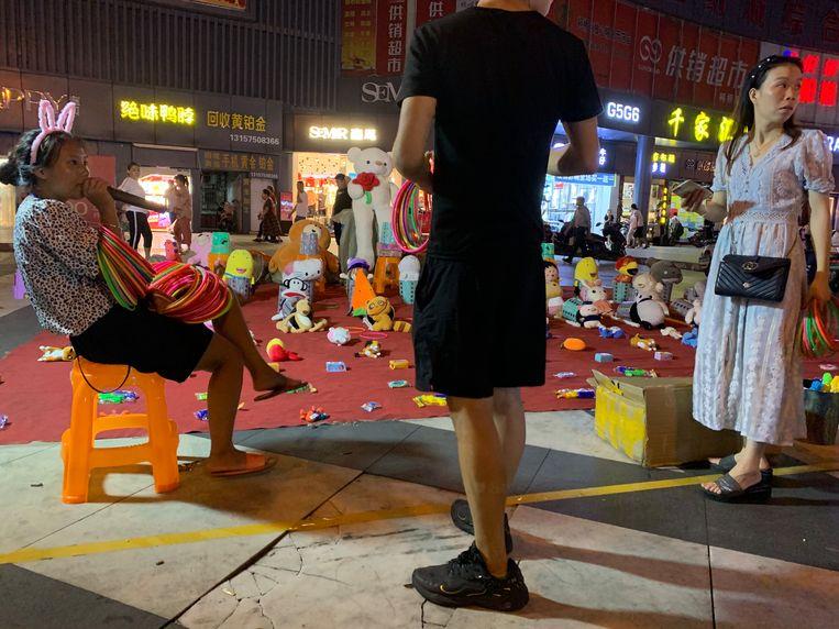 Straatverkoper Liang Jie met het haar ringenspel en knuffels in Shanghai, China Beeld Eefje Rammeloo