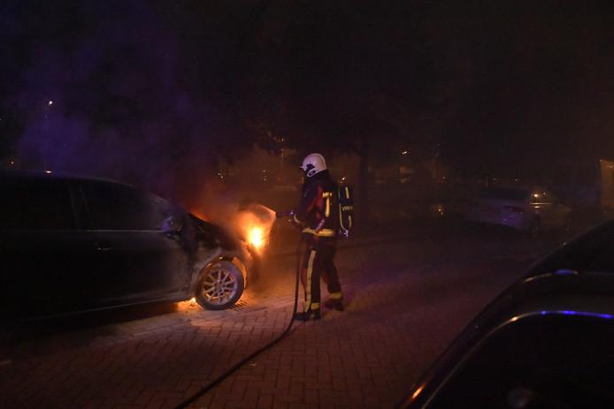 De brandweer blust de auto die in de nacht van maandag op dinsdag uitbrandde aan de Da Costakade in Gouda.