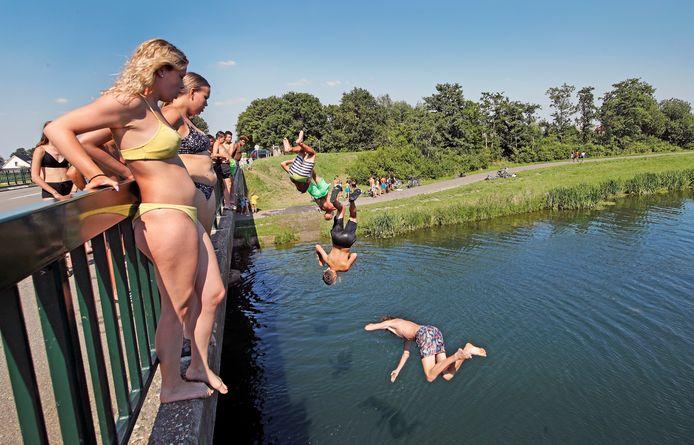 Meiden kijken toe welke jongens de mooiste duik maken, vanaf de brug over de Bernisse bij Zuidland.