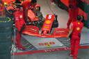 Ferrari-monteurs vervangen de vleugel op de wagen van Vettel.