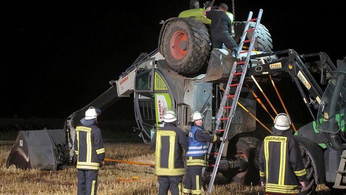 Duitse brandweermannen proberen de in Isselburg gekantelde kraan weer op zijn wielen te hijsen.