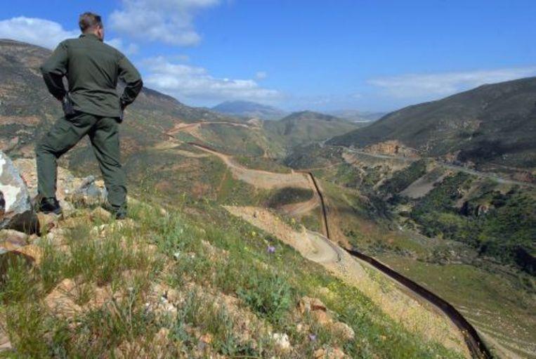 Een Amerikaanse grenswacht kijkt uit over een deel van een kilometers lang hekwerk op de grens met Mexico. ANP Beeld
