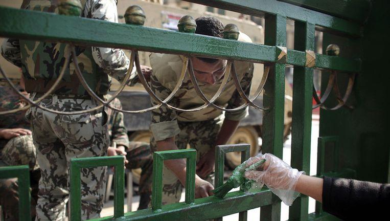 Het normale leven in Egypte is weer wat op gang, hier wordt een beschadigd hek op het Tahrirplein in Caïro opnieuw geschilderd. Beeld ap