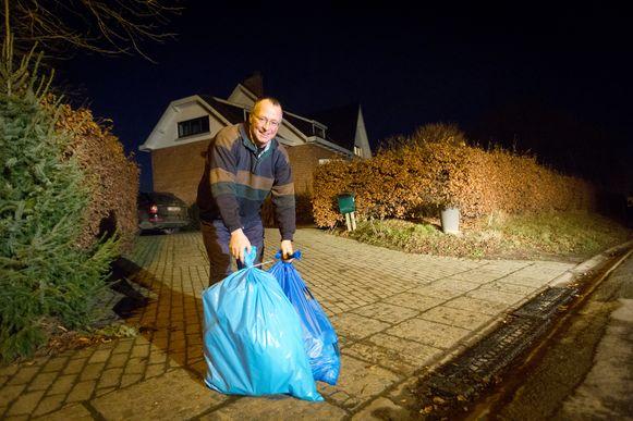 Burgemeester Claudy Prosmans zet de vuilzakken buiten. Voortaan zal het aanbieden van huisvuil niet meer gratis zijn voor de inwoners.