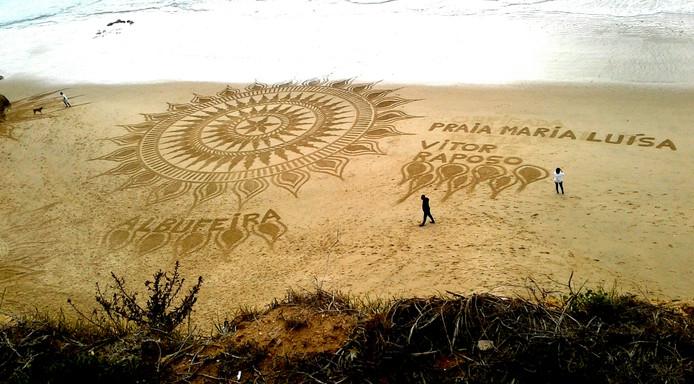 Iedere dag worden deze vakantiegangers verrast door een nieuwe zandtekening door strandkunstenaar Vitor Raposo.  De tekening blijft staan tot de vloed ze weer verwijdert.