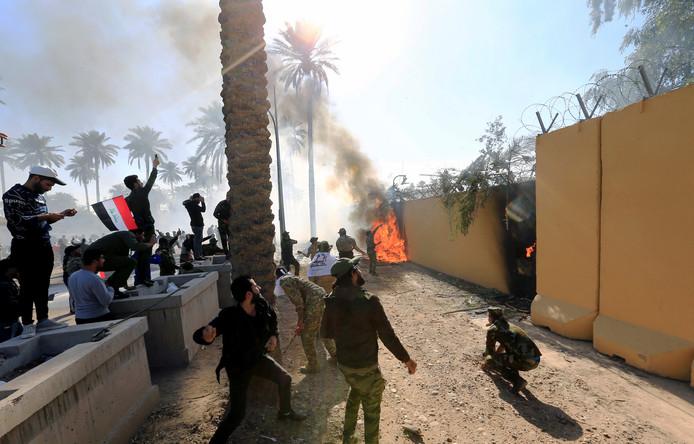 De woedende menigte voor bij de Amerikaanse ambassade in Bagdad. Er is vuur en er klinken geweerschoten.