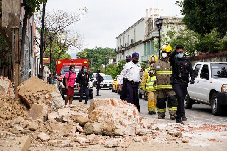 Politie en brandweer inspecteren de schade aan een gebouw in Oaxaca.