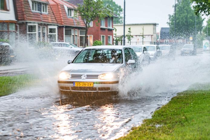 Een auto rijdt door een ondergelopen straat in Sappemeer nadat een hevige regenbui overgetrokken is.