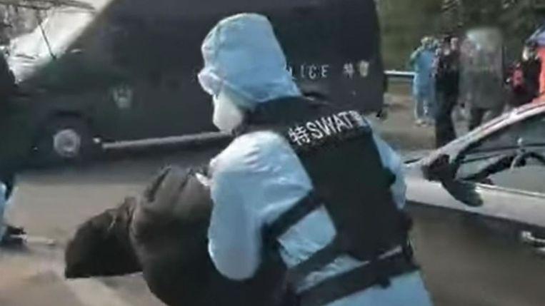 Een vrijwilliger wordt na zijn arrestatie afgevoerd.