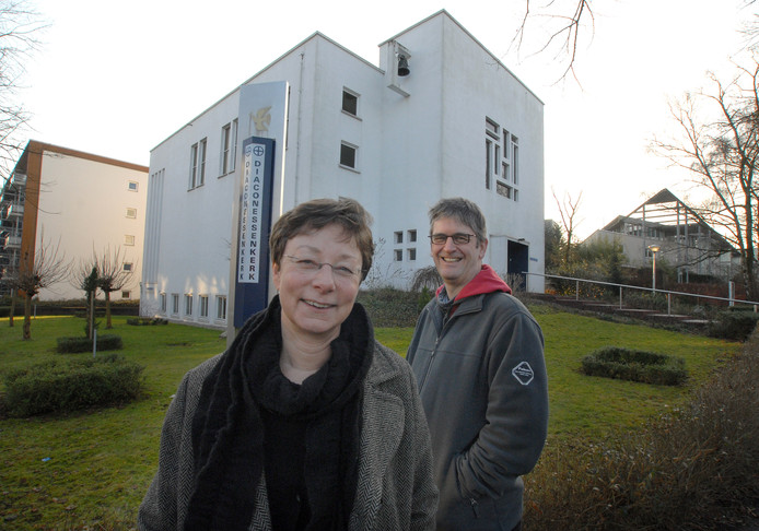 Dominee Monique Maan en ouderling Peter Hoeve staan voor de Diaconessenkerk uit 1959. Het is één van de kerken die in de verkoop gaat. De foto is uit het archief.