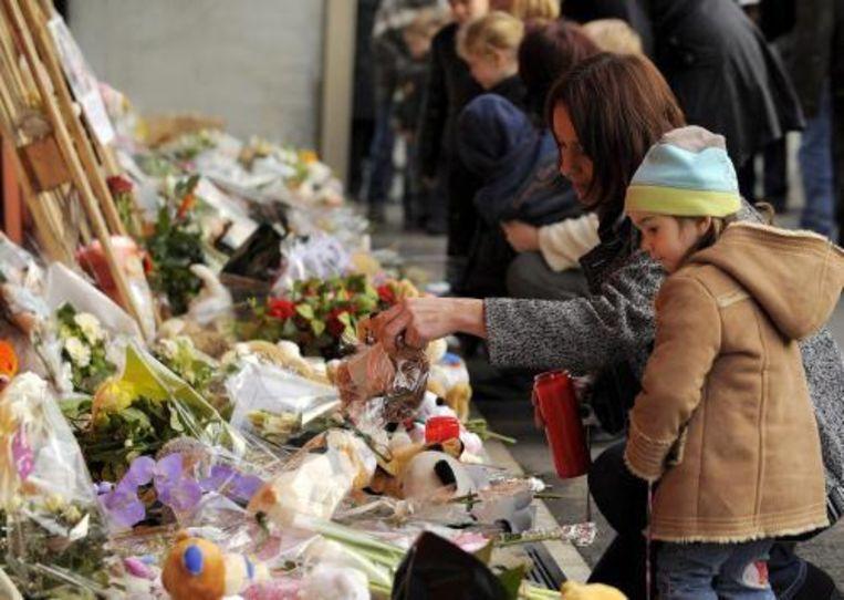 Rondom het kinderdagverblijf in Dendermonde, waar een geschminkte man vrijdag twee baby's en een leidster doodstak, is zaterdag een grote toeloop van mensen die hun medeleven betuigen. Foto ANP Beeld