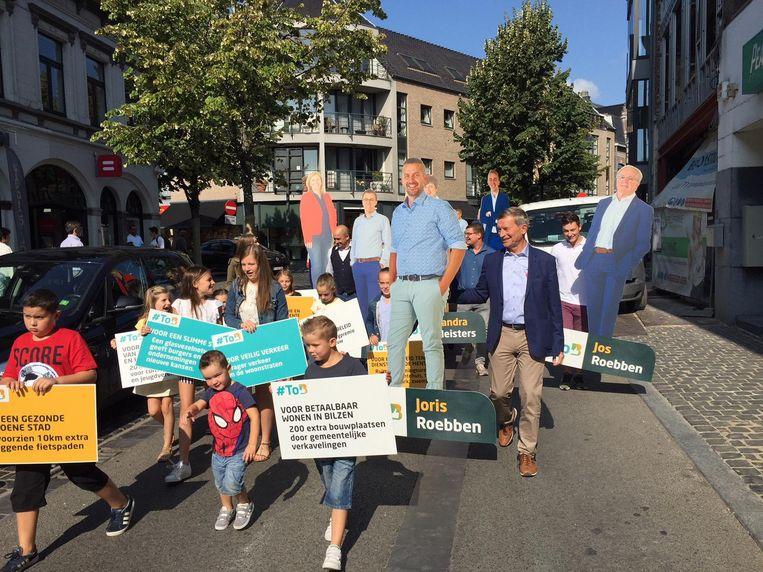 Kandidaten voor TOB (Trots Op Bilzen) trekken samen met de jeugd en hun kartonnen evenbeeld door de straten van Bilzen.