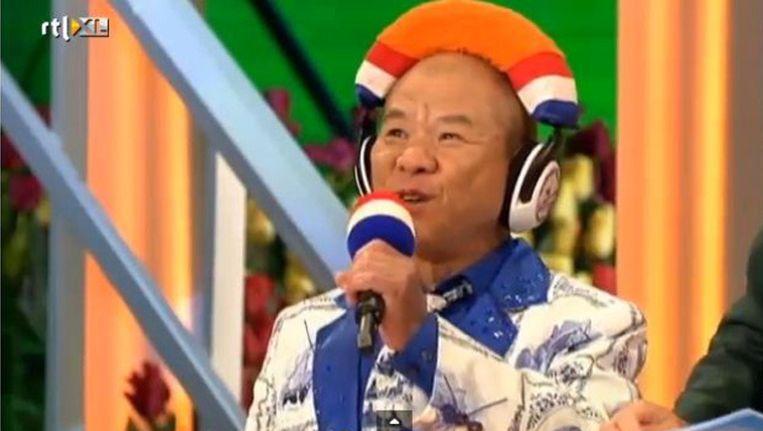 Boven en onder: In het RTL-programma Ik hou van Holland zingt de Chinese 'meneer Cheung' onverstaanbaar Nederlandse liedjes. Panels met bekende Nederlanders lachen om zijn gebrabbel en proberen te raden wat hij zingt. 'Onze kleine Ik hou van Hollandheld', zoals presentatrice Linda de Mol hem wel noemt ¿ zij spreekt tegen hem als tegen een kind - zorgt voor veel hilariteit in de studio. Beeld RTL
