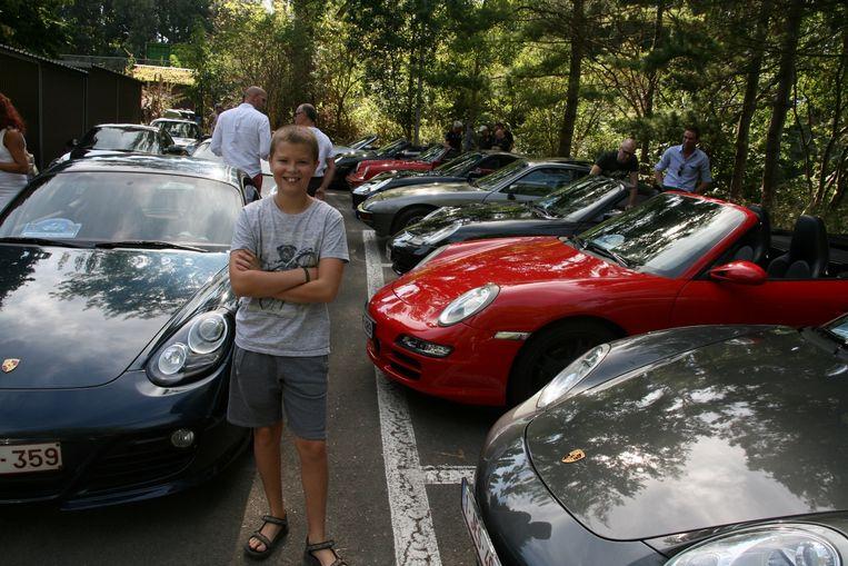 De 11-jarige Arne poseert fier tussen de dure sportwagens.