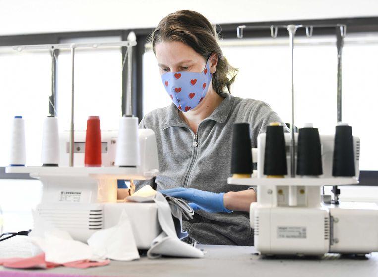 Een medewerker van The Fashion Filter produceert een mondkapje. Beeld ANP