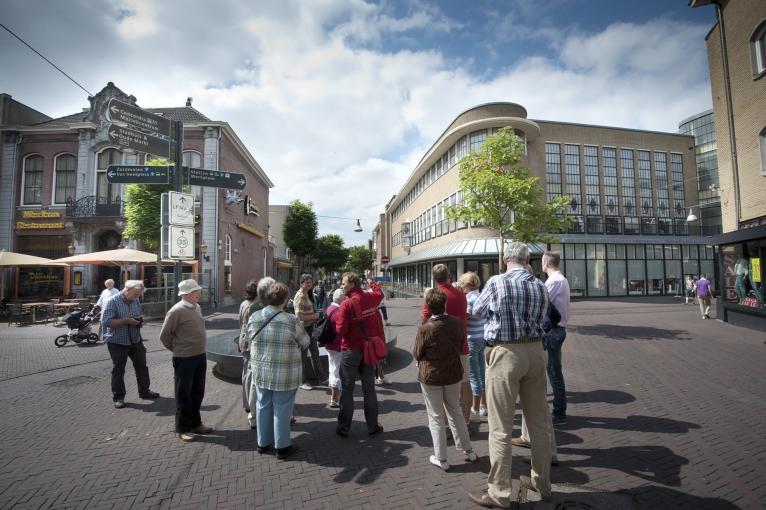 Op kruispunt De Graaff, de plek waar zes straten bijeenkomen, vertelt stadsgids Robin Pater (rood jack) boeiende verhalen over het verleden van Enschede. foto Reinier van Willigen