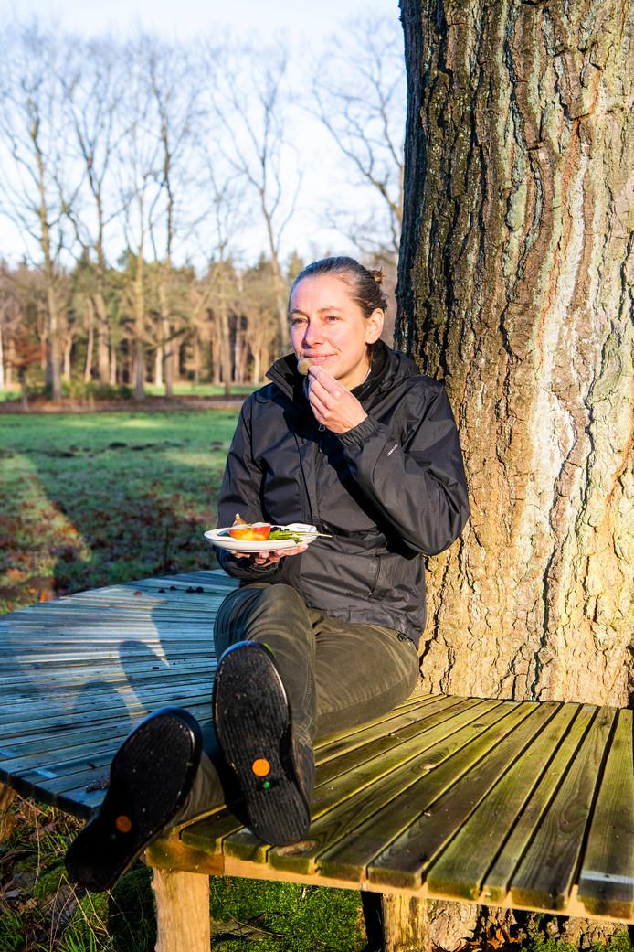 Sabine Philips met een bordje bessen, een appel en vijgen tegen een boom aangeleund op het terrein waar ze een voedselbos wil realiseren. In dat bos zijn op termijn deze vruchten zelf te vinden.