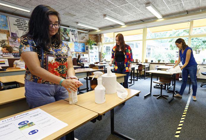 Vrinda Gautam (links) en Nina van den Heuvel (midden) kunnen sinds 2 juni weer naar school op het Elde College. Strepen op de vloer en handpompjes met handgel maken duidelijk dat tijden veranderd zijn door het coronavirus.