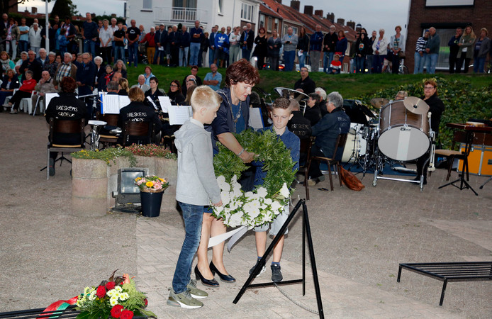 Mat de Ruijsscher (links) en Cas Versprille helpen burgemeester Marga Vermue met het leggen van een krans.