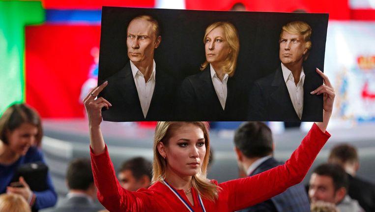 Een journalist houdt een afbeelding vast met portretten van Poetin, Le Pen en Trump. (Archiefbeeld 2016) Beeld epa