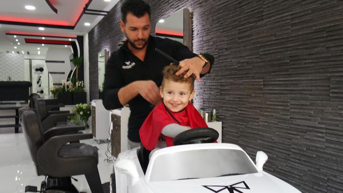 Kapper Cihat Ozgul knipt de kleine Davud. Die vindt het wel prima in zo'n witte 'Bentley'.