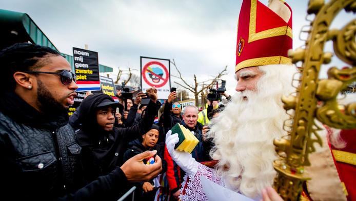 Sinterklaas krijgt schuursponsjes van een tegenstander van zwarte Piet, om het gezicht schoon te poetsen