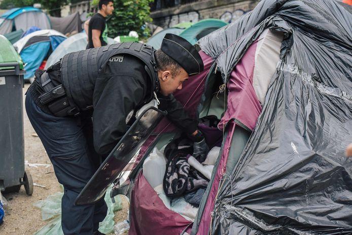 Een Franse agent doorzoekt een tentenkamp van migranten.