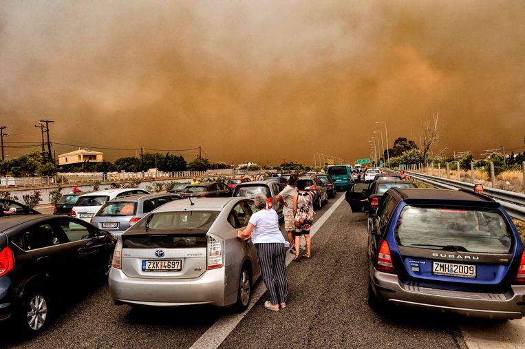 Terwijl de lucht helemaal oranje kleurt, proberen honderden inwoners weg te komen uit Kineta.  Beeld AFP