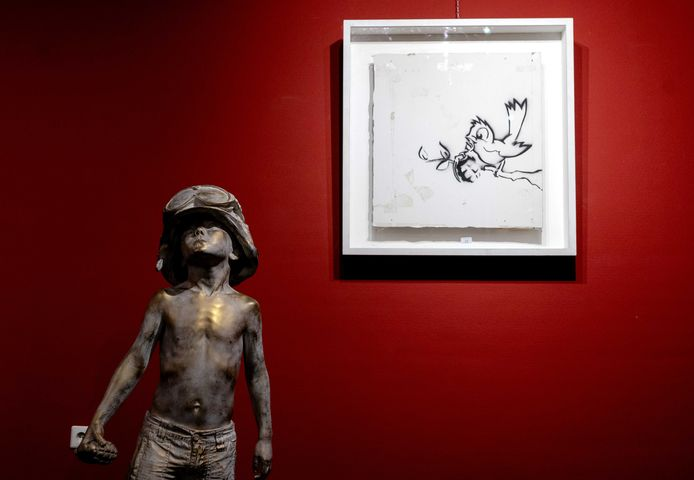 Graffitischilderij Bird with Grenade van kunstenaar Banksy is donderdagmiddag in Zwolle geveild voor 170.000 euro. Op de voorgrond Boy Soldier, van de Britse kunstenaar Schoony.