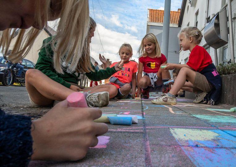 De kinderen tekenen met krijt op de stoep voor het huis van de buur en zijn echtgenote.