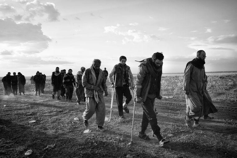 Gewonden mannen ontvluchten Baghouz, het laatste bastion van IS.  Beeld Eddy van Wessel